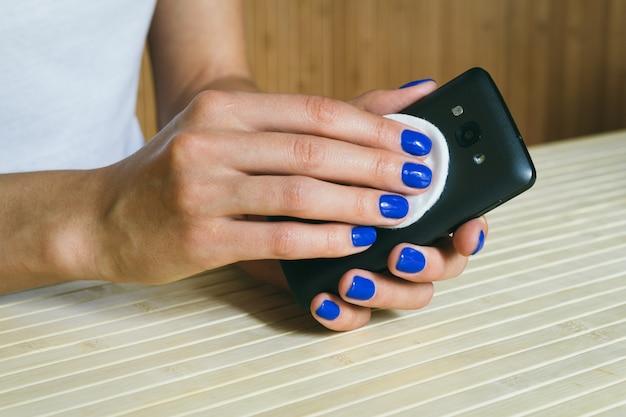 Manos femeninas limpian de polvo y suciedad un teléfono móvil de color negro.