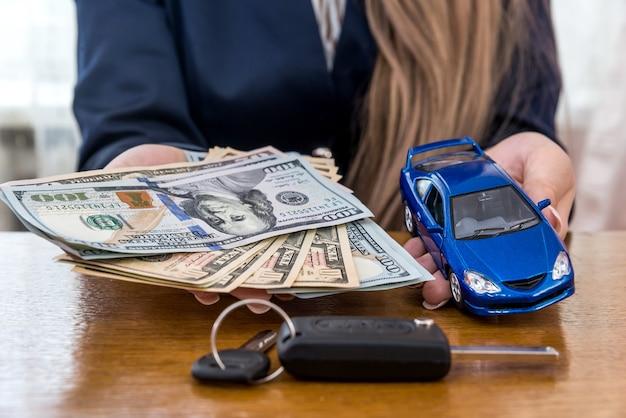 Manos femeninas con llaves y coche de dólares