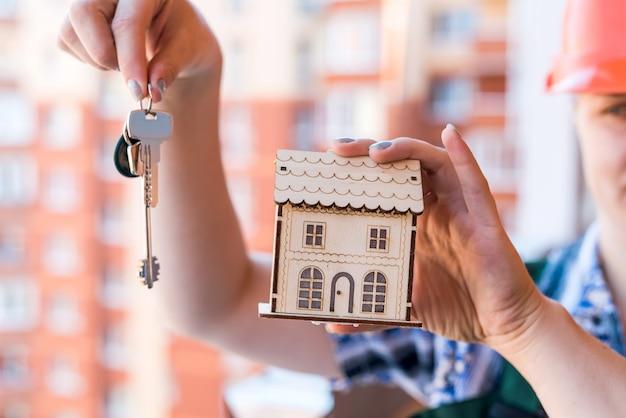 Manos femeninas con llaves y modelo de casa de madera