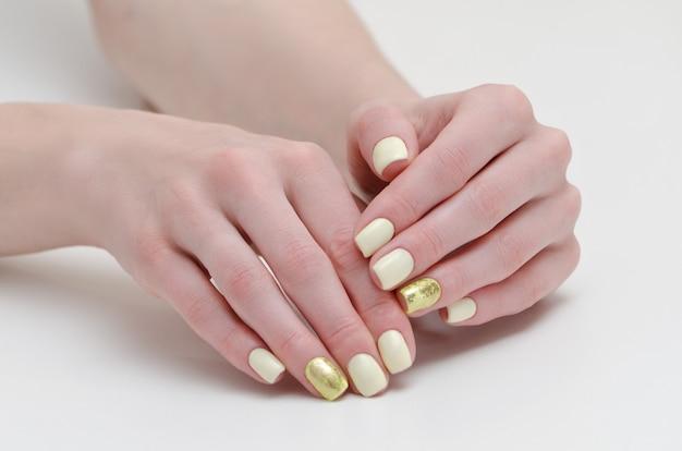 Manos femeninas con manicura, amarillo con cubierta de uñas de oro.