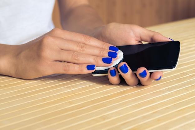 Las manos femeninas con manicura azul limpian la pantalla del teléfono