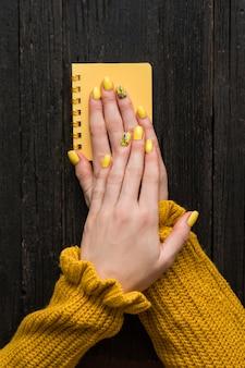 Manos femeninas con una manicura en un bloc de notas amarillo