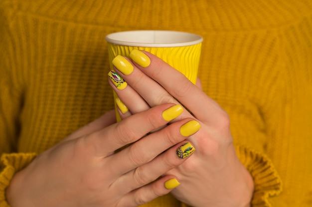 Manos femeninas con una manicura brillante y una taza de papel amarillo.