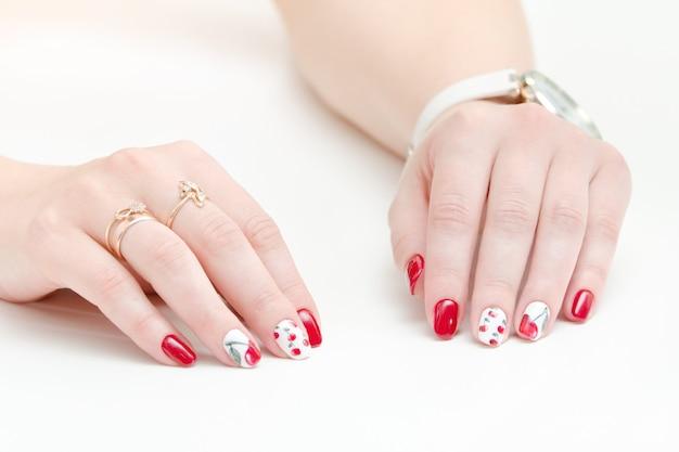 Manos femeninas con manicura, esmalte de uñas rojo, dibujo con cerezas. fondo blanco.