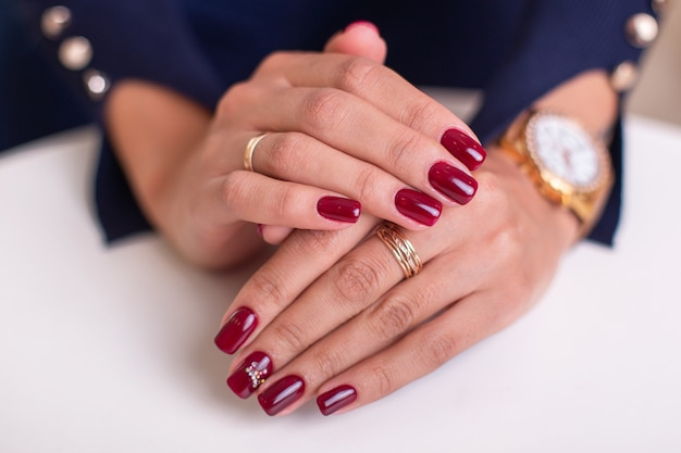 Manos femeninas con uñas de manicura de lujo, esmalte de gel rojo vino sobre blanco