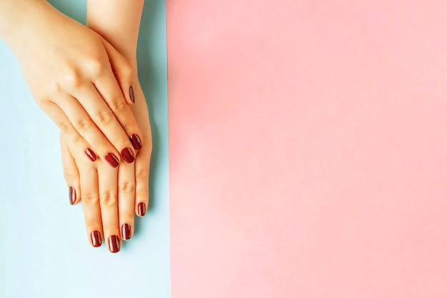 Manos femeninas con manicura roja sobre un fondo rosa y azul, vista superior