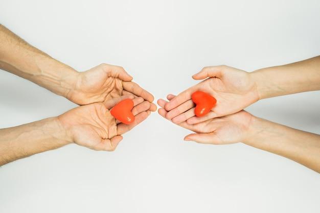 Las manos femeninas y masculinas sostienen figuras de corazón en las palmas. concepto de caridad, parejas, relaciones, amor. concepto de san valentín