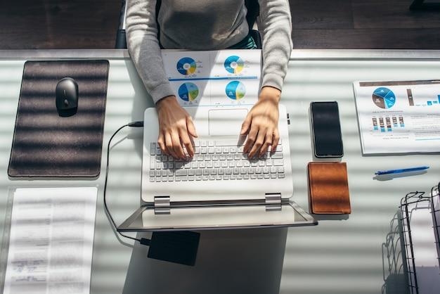 Manos femeninas en la mesa de trabajo con ordenador portátil y vista de documentos desde arriba.