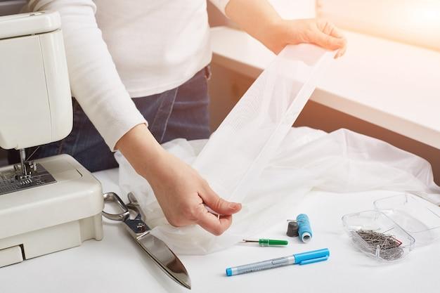 Manos femeninas de una modista. niña con máquina de coser y accesorios