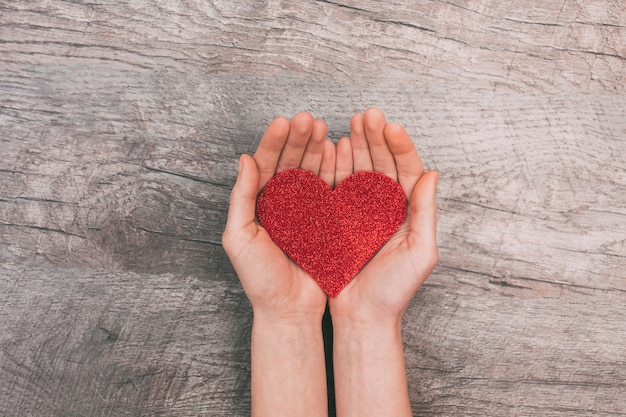 Manos femeninas mostrando corazón de papel rojo, sobre fondo de madera