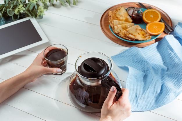 Manos femeninas y panqueques con jugo. desayuno saludable