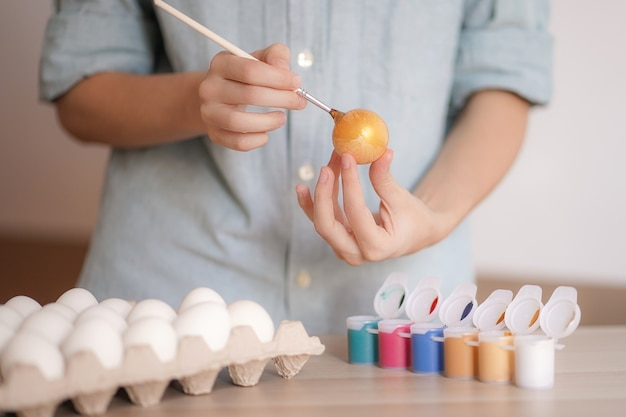 Manos femeninas pinta huevo con pintura dorada para pascua