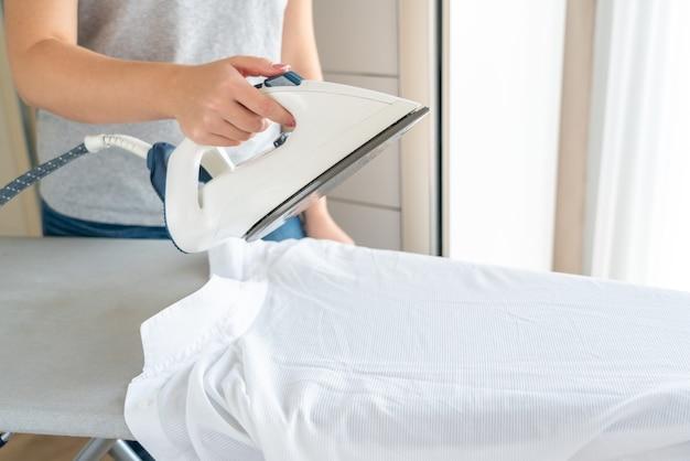 Manos femeninas planchar camisa blanca en tabla de planchar