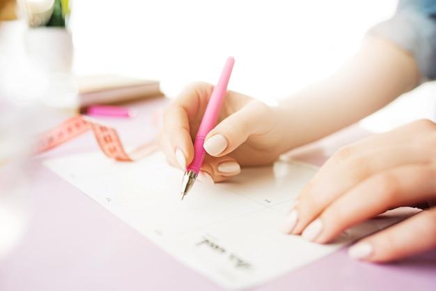Manos femeninas con pluma. escritorio rosa de moda.