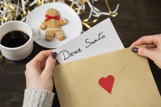 Manos femeninas ponen una carta para santa en un sobre, pan de jengibre y café