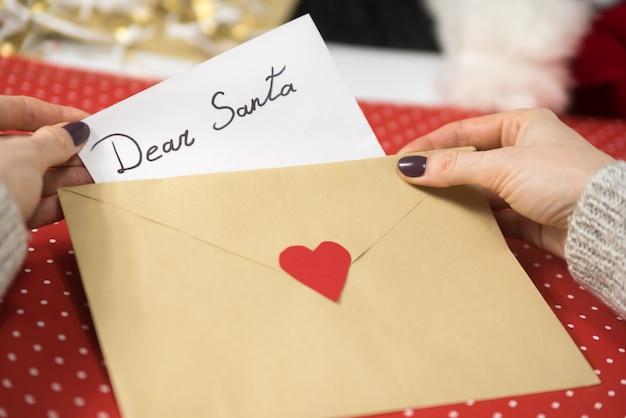 Manos femeninas ponen una carta para santa en un sobre