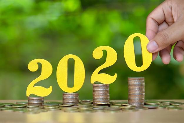 Manos femeninas poniendo oro número 2020 de madera en la pila de monedas.
