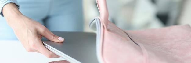 Manos femeninas poniendo el portátil en la bolsa en casa concepto de accesorios para portátiles de primer plano