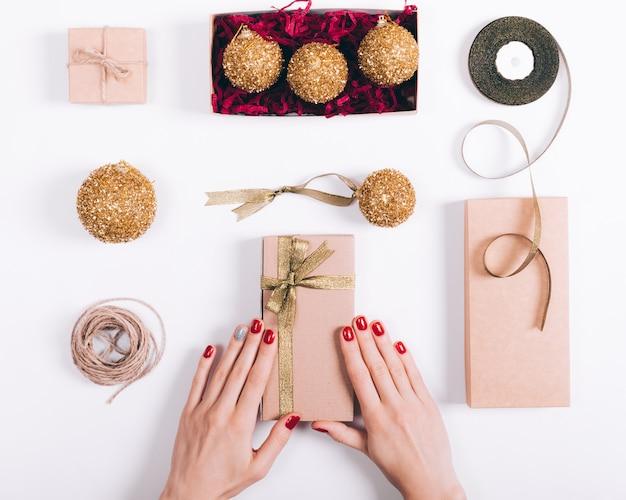Manos femeninas preparan adornos navideños