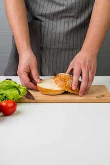 Manos femeninas preparando una hamburguesa