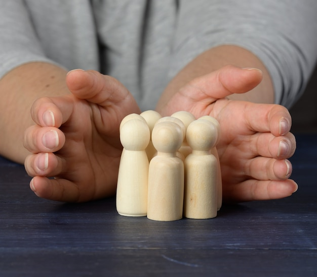 Las manos femeninas protegen las figuras de madera de los hombres. concepto de protección y tutoría. preservación del equipo en tiempos de crisis, trabajo en equipo