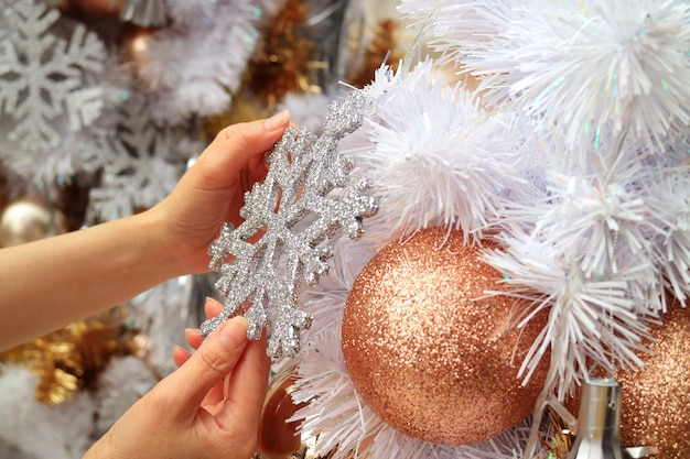 Manos femeninas que adornan el árbol de navidad con un adorno en forma de copo de nieve brillante