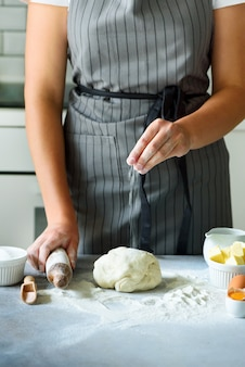 Manos femeninas que amasan la pasta, fondo que cuece. cocinando ingredientes