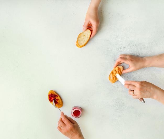 Manos femeninas que ilustran las etapas de hacer sándwich de mantequilla de maní y mermelada, vista superior, espacio de copia