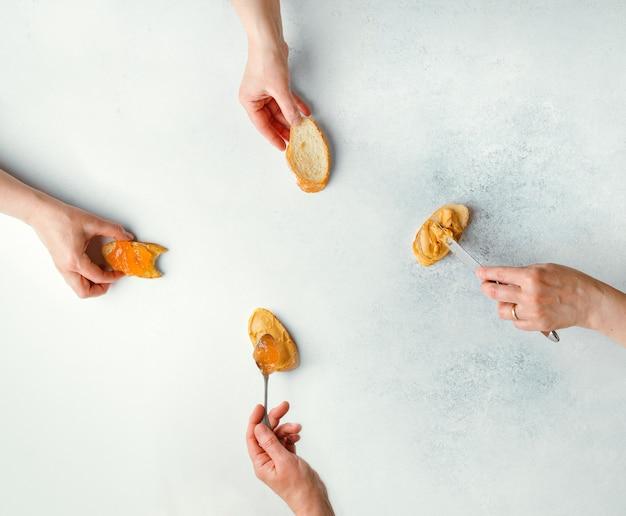 Manos femeninas que ilustran las etapas de hacer sándwich de mantequilla de maní y mermelada, vista superior