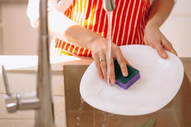 Manos femeninas que lavan doshes de cerca