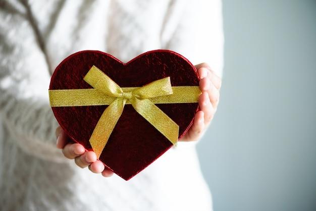 Las manos femeninas que llevan a cabo el corazón de la caja de regalo forman en gris.