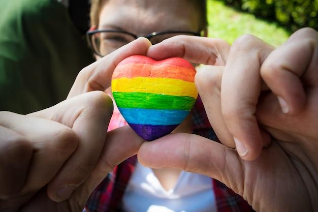 Manos femeninas que llevan a cabo el corazón decorativo con las rayas del arco iris.