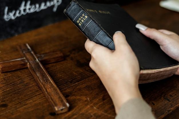 Manos femeninas que sostienen una biblia y una cruz de madera