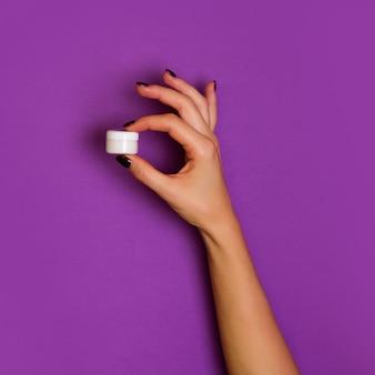 Manos femeninas que sostienen la botella cosmética blanca en el fondo violeta