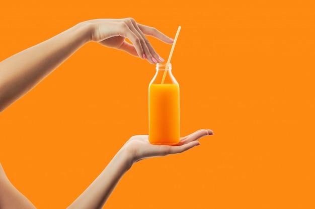 Manos femeninas que sostienen la botella con paja de zumo de naranja fresco de desintoxicación