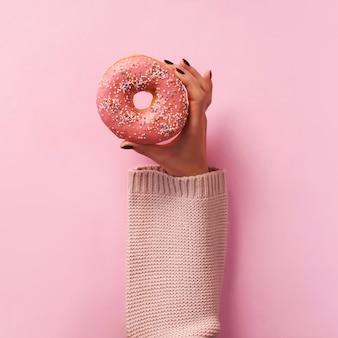 Manos femeninas que sostienen el buñuelo sobre fondo rosado.