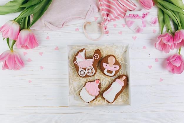 Manos femeninas que sostienen la caja con las galletas. una composición para recién nacidos