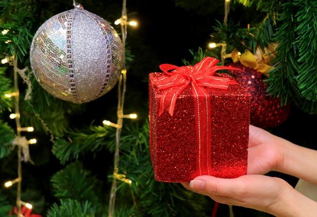 Manos femeninas que sostienen una caja de regalo de brillo rojo con adorno de bola de lentejuelas plateadas
