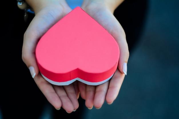 Manos femeninas que sostienen la caja de regalo en forma de corazón.