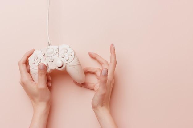 Manos femeninas que sostienen una palanca de mando rosada en sus manos aisladas en un fondo rosado