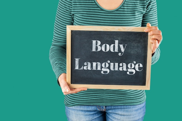 Manos femeninas que sostienen una pequeña pizarra negra delante del cuerpo con palabras escritas que dicen lenguaje corporal