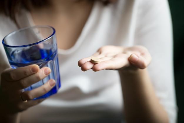 Manos femeninas que sostienen la píldora y el vidrio de agua, opinión del primer