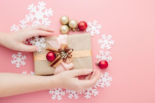 Manos femeninas que se sostienen presentes con el arco en rosa. telón de fondo festivo para vacaciones: cumpleaños, día de san valentín, navidad, año nuevo. lay flat