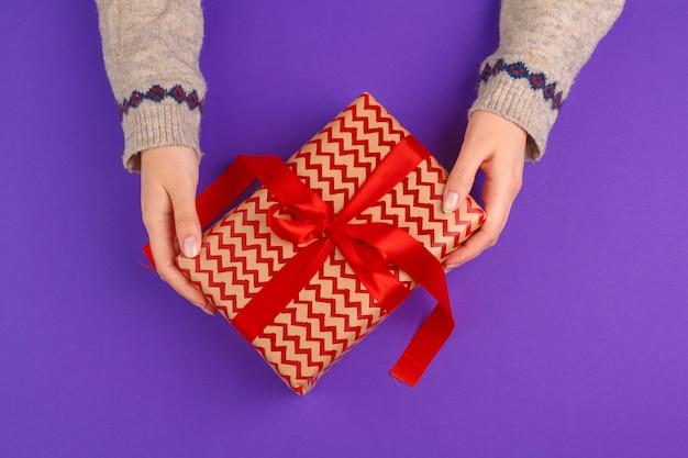 Manos femeninas que sostienen el regalo envuelto en fondo púrpura