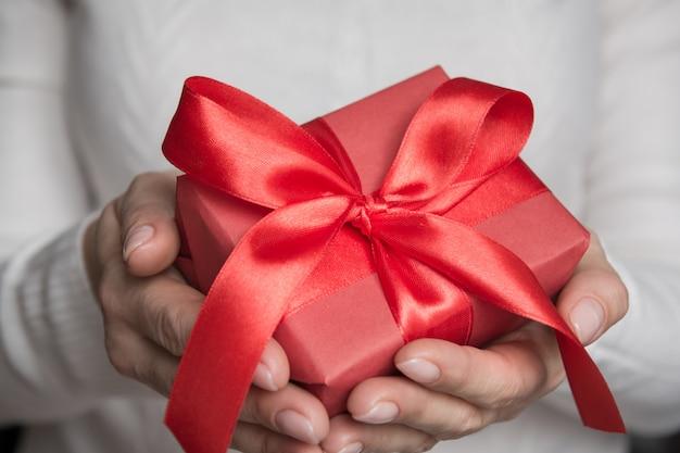Manos femeninas que sostienen el regalo rojo envuelto con la cinta roja del arco. de cerca. navidad