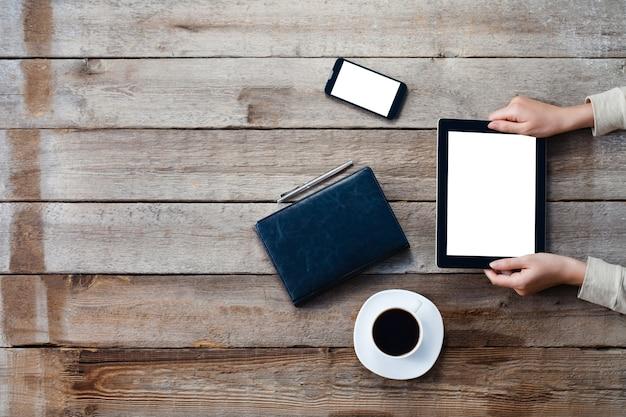 Manos femeninas que sostienen la tableta digital con la pantalla aislada sobre la vieja mesa de madera gris.