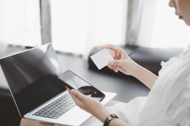 Manos femeninas que sostienen la tarjeta de crédito y que usan la computadora portátil para las compras en línea.