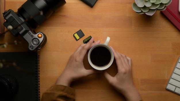 Manos femeninas que sostienen la taza de café en la mesa de trabajo de madera con material de oficina