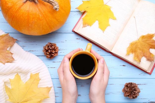 Manos femeninas que sostienen la taza de café negro con hojas de otoño