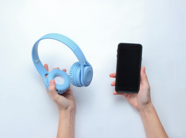 Manos femeninas que sostienen un teléfono inteligente moderno y auriculares sobre fondo gris